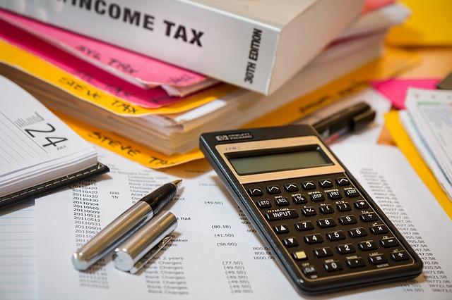 kalkulačka na papírech, vedle propiska, deník a spousta dalších papírů i růžové a žluté