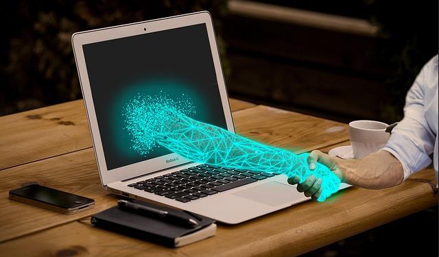 Notebook leží na stole, u něj sedí člověk a z obrazovky se vynořuje ruka a třese si s člověkem